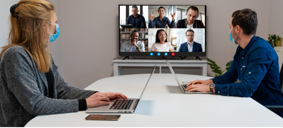 A hybrid team meeting, two members in person with masks, 6 team members on video conference.